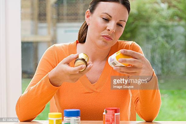 woman choosing between supplements - nutritional supplement stock pictures, royalty-free photos & images