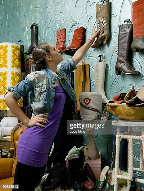 woman choosing boots in second-hand store