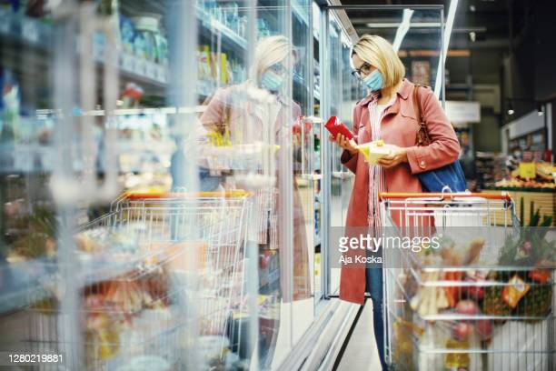 woman choosing cheese in supermarket. - frozen food stock pictures, royalty-free photos & images