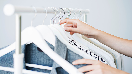 Woman choosing clothes on a rack 1024286974