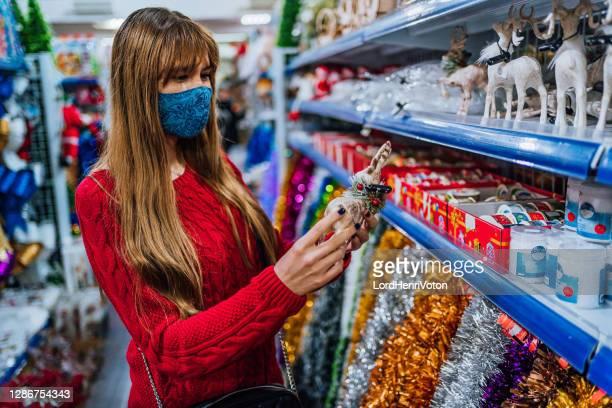 mujer eligiendo decoraciones para navidad - henri coste fotografías e imágenes de stock