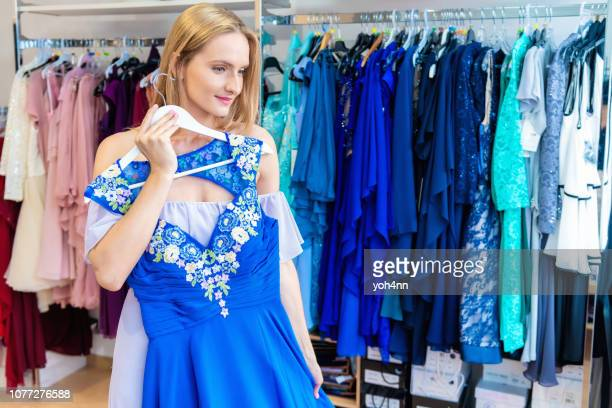 woman choosing dress at clothing store - blue dress stock pictures, royalty-free photos & images