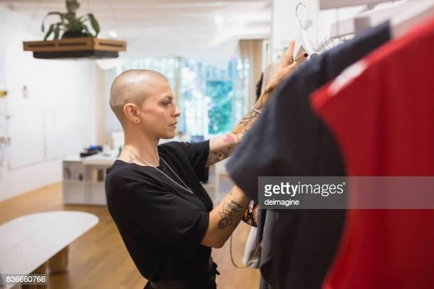 Woman choosing dress in clothing store