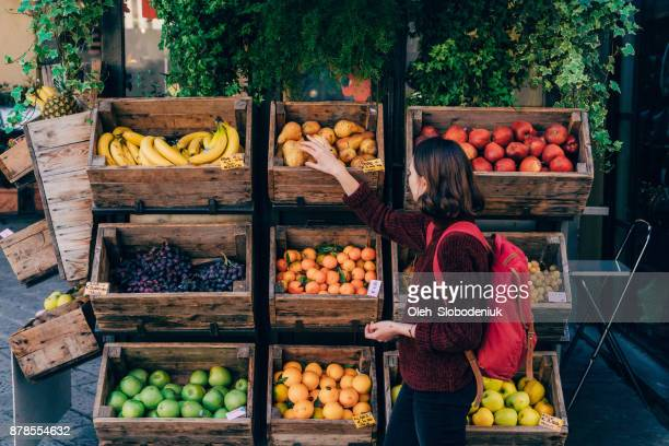 Woman choosing fresh fruits on the street of Florence