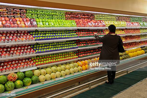 woman choosing fresh fruits - abundance stock pictures, royalty-free photos & images
