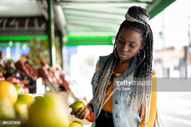 woman choosing fruits on street market - caribbean culture stock pictures, royalty-free photos & images
