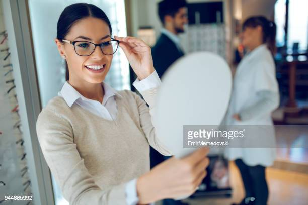 woman choosing glasses in optical store using mirror - spectacles stock pictures, royalty-free photos & images