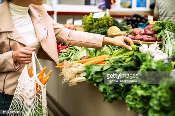 woman choosing greenery and vegetables at farmer market and using reusable eco bag. - saco objeto manufaturado imagens e fotografias de stock