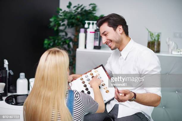 Woman choosing hair color from palette in hair salon