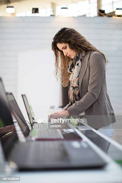 woman choosing laptop - electronics store stock photos and pictures