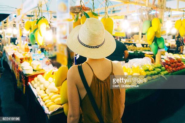 Woman choosing mango in market