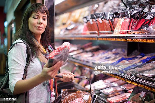 Woman choosing meat in butcher's shop