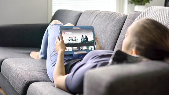 Woman choosing movie from online stream service with tablet. Watching series with on demand video (VOD) website concept. Streaming digital film from site by tv network. 1158779001
