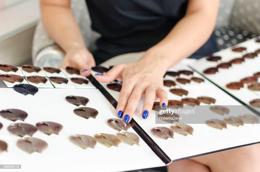 Woman choosing new hair color : Stock Photo