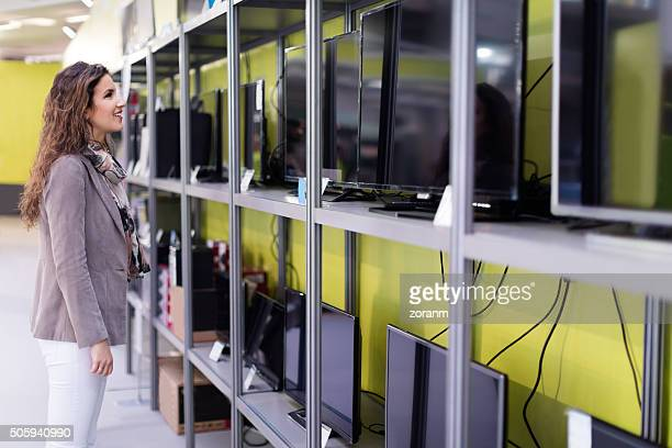 woman choosing new tv - electronics store stock photos and pictures