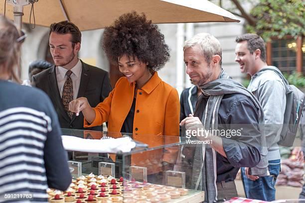 Woman choosing pastries at food stall at city market