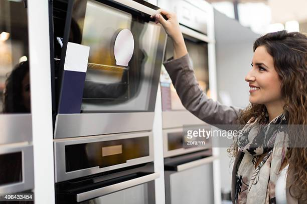 woman choosing stove - appliance stock pictures, royalty-free photos & images