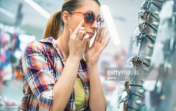 Woman choosing sunglasses at a retailer.