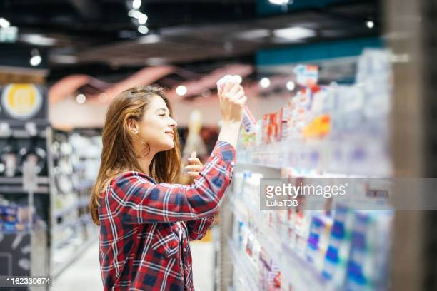 woman choosing sunscreen lotion stock photo - pharmacy stock pictures, royalty-free photos & images
