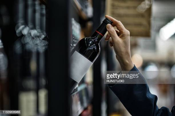 woman choosing wine bottle in liquor store - alcohol drink stock pictures, royalty-free photos & images