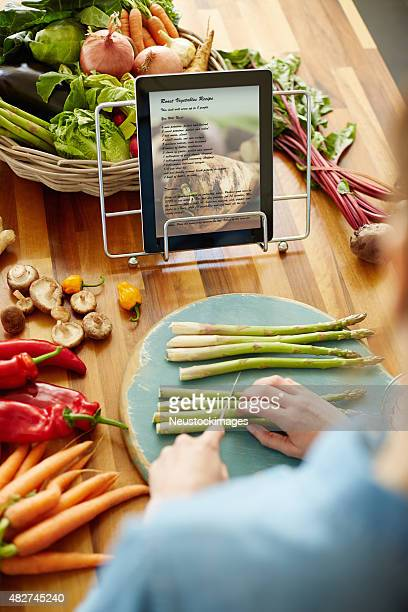 Woman chopping asparagus in front of recipe on digital tablet