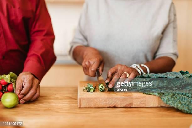 vrouw hakken chard op cutting board door man - snijden stockfoto's en -beelden