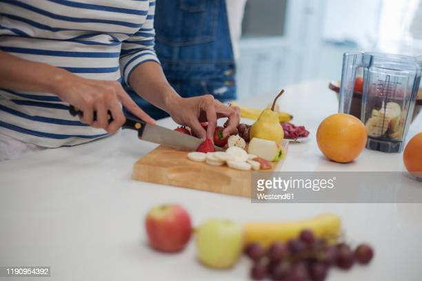 woman chopping fruits in kitchen, preparing smoothie - chopped stock pictures, royalty-free photos & images
