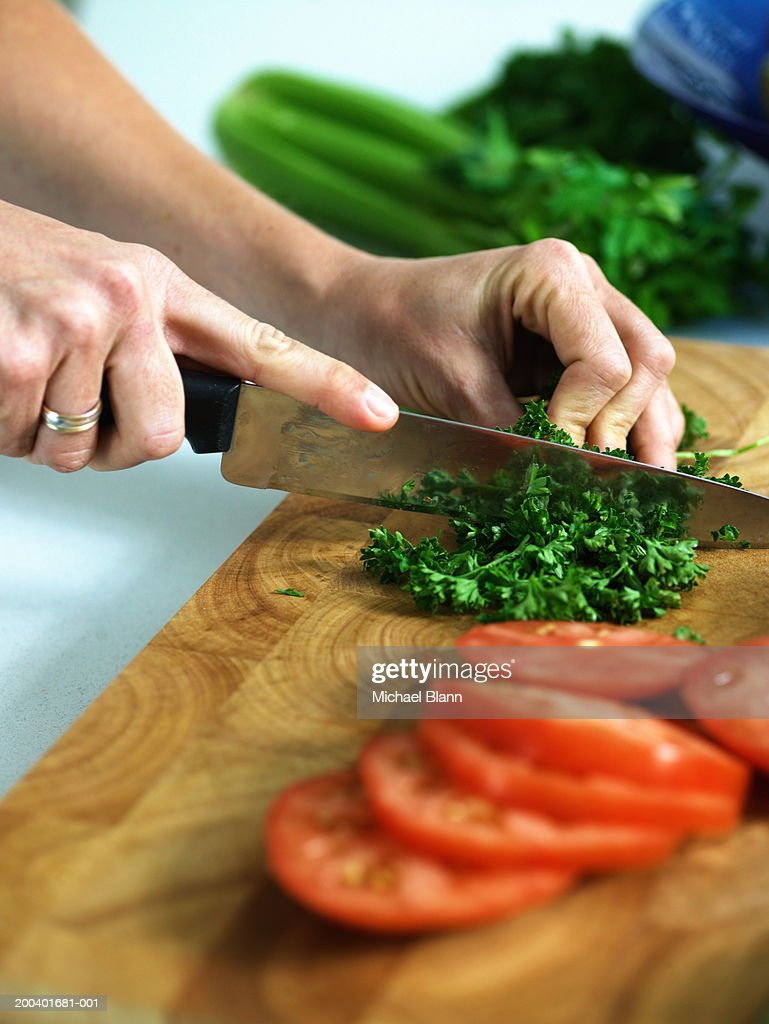 Woman chopping herbs, close-up : Stock Photo