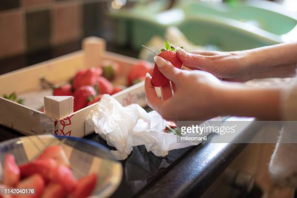 woman chopping strawberries - chopped stock pictures, royalty-free photos & images