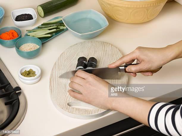 Woman chopping sushi at table
