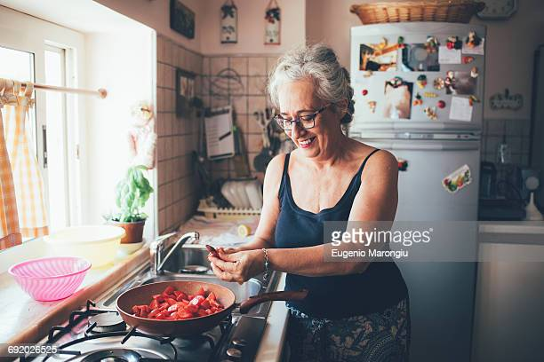 woman chopping tomatoes into saucepan smiling - italian women stock photos and pictures