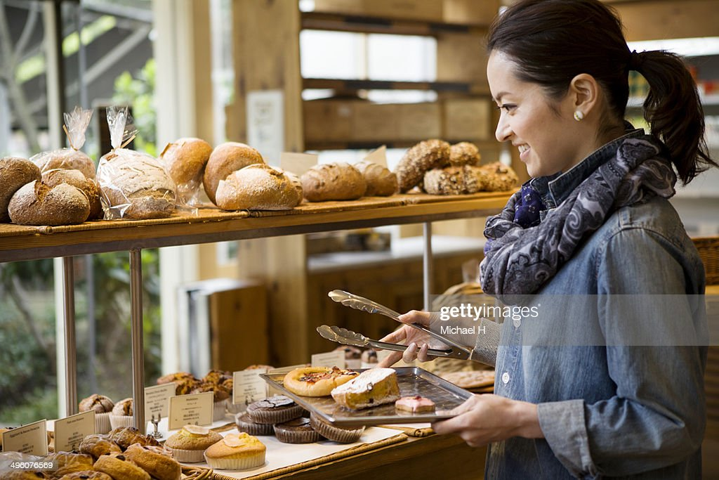 A woman chosing breads in bakeryshop. : Stock Photo