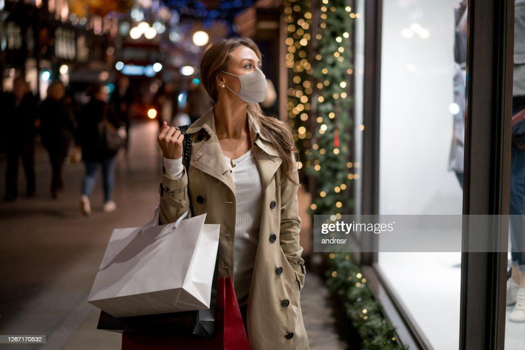 Woman Christmas shopping wearing a facemask : Stock Photo