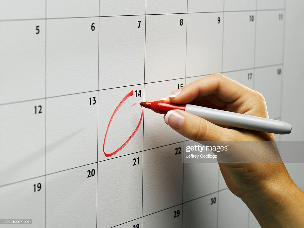 Woman circling day on wall calendar, close-up : Stock Photo