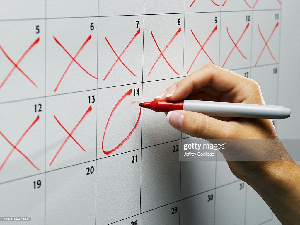 Woman circling day on wall calendar, close-up : Stock Photo