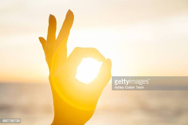 Woman circling the sun with fingers at sunrise