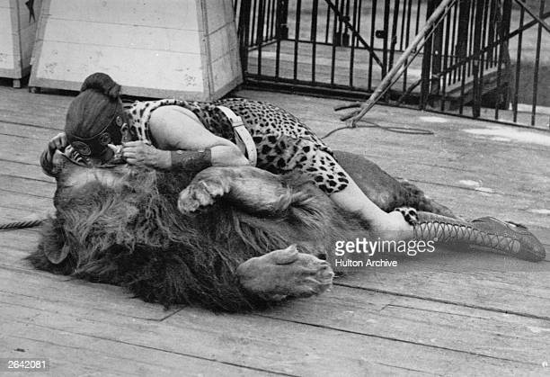 A woman circus performer dressed in a leopard skin gladiator costume places her head in a lion's mouth
