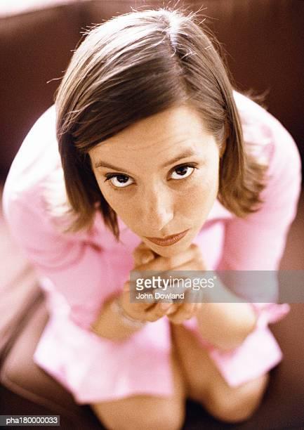 woman clasping hands under chin, elevated view, portrait - mulher orando de joelhos imagens e fotografias de stock