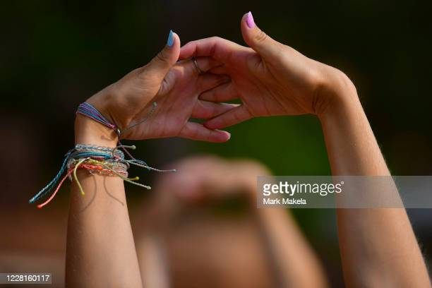 Woman clasps her hands during a stretch while participating in a morning yoga session on August 22, 2020 at the Red Rocks Amphiteatre in Morrison,...