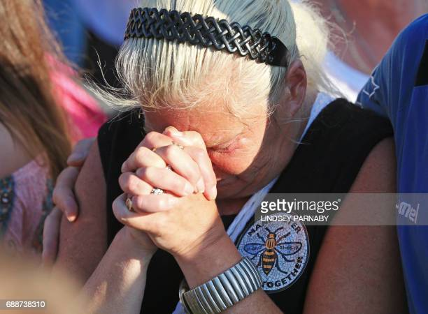 A woman clasps her hands in front of her face during a vigil to commemorate the victims of the May 22 attack on Manchester Arena at Tandle Hill...