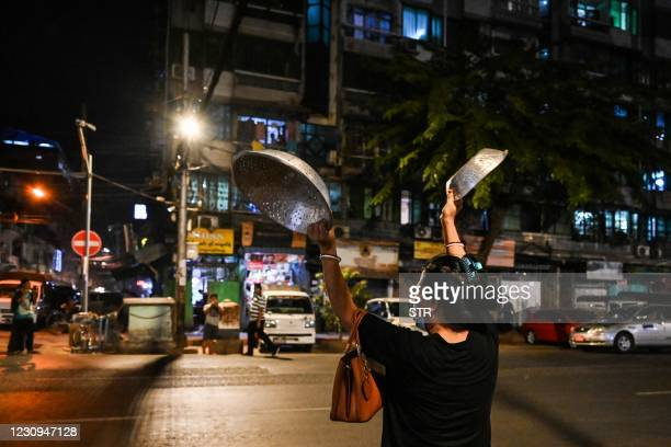 Woman clatters pans to make noise after calls for protest went out on social media in Yangon on February 3 as Myanmar's ousted leader Aung San Suu...