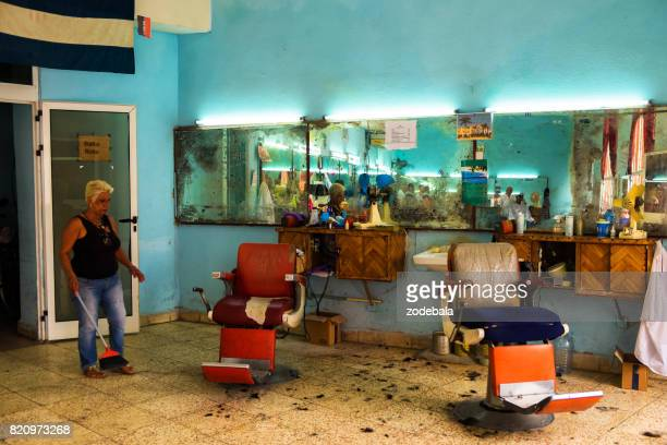 Woman Cleaning a Barber Shop in Cuba