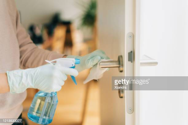 woman cleaning a door handle with a disinfection spray and disposable wipe - disinfection stock pictures, royalty-free photos & images