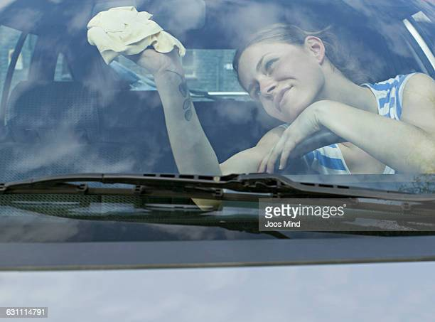 woman cleaning car window