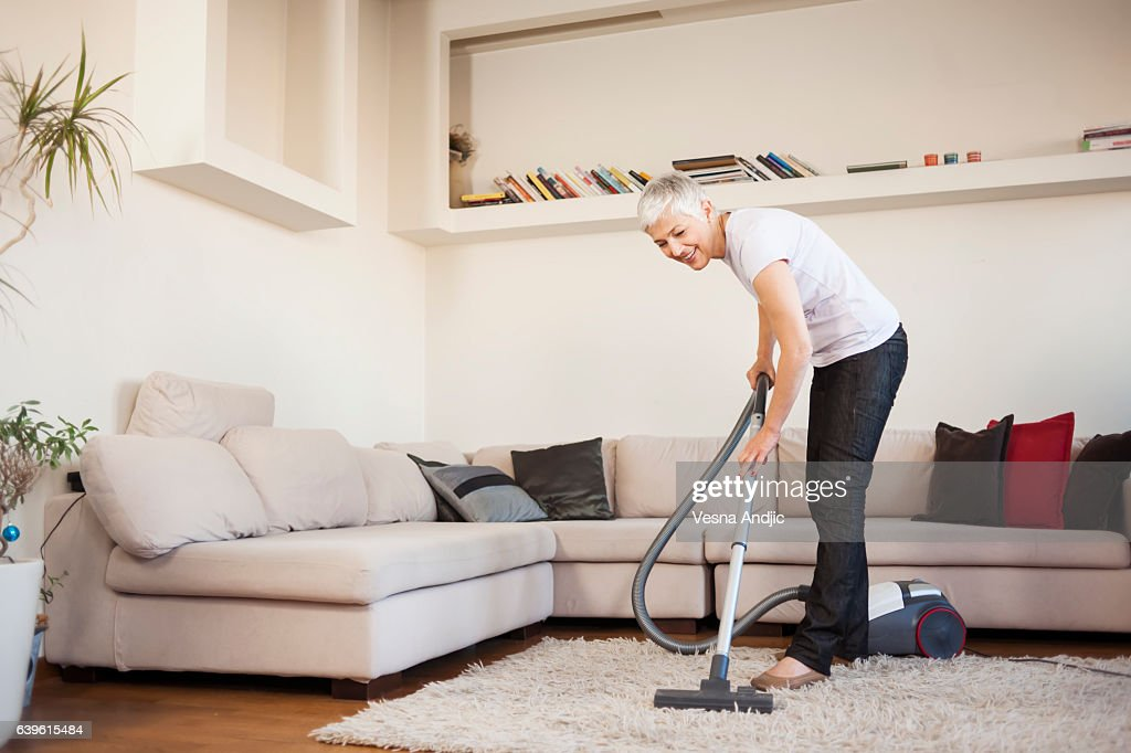 Woman cleaning carpet with a vacuum cleaner in room : Stock Photo