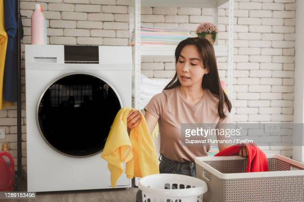 woman cleaning clothes at laundry - laundry stock pictures, royalty-free photos & images