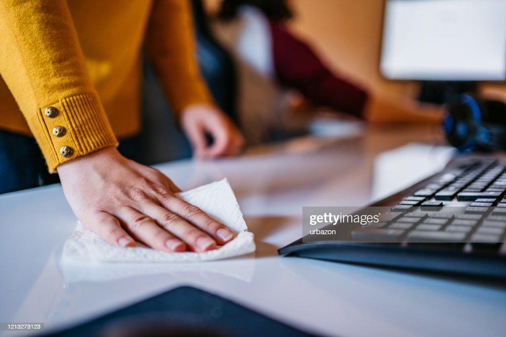 オフィスでコンピュータデスクを掃除する女性 : ストックフォト