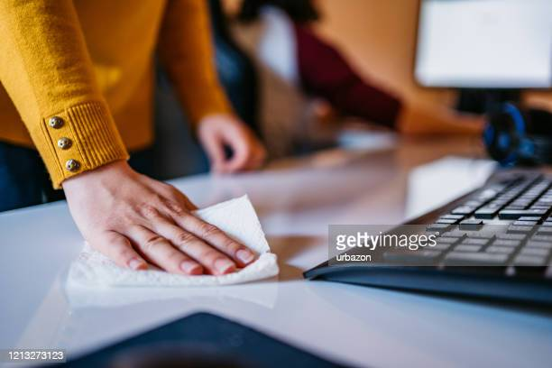 woman cleaning computer desk in office - disinfection stock pictures, royalty-free photos & images