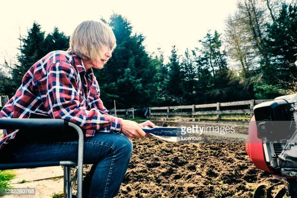 woman cleaning dirt from a garden rotovator - one senior woman only stock pictures, royalty-free photos & images