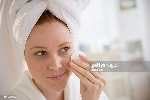 Woman cleaning face with cleansing pad